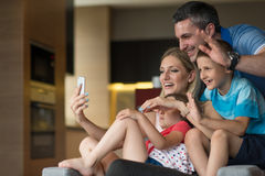 Family having fun at home. Happy family siting on sofa and using cell phone for video call at home stock image