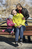 The happy family sits on a bench in the park. Royalty Free Stock Images