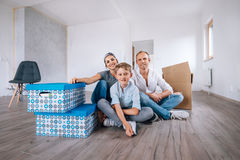 Happy family sits on floor in their new home Stock Photography