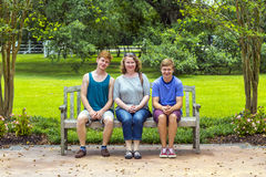 Happy family sits in the garden at Royalty Free Stock Photography