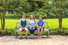 Happy family sits in the garden at Stock Photography