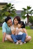 Happy family sits on grass field. Happy family of three sits on green grass field Royalty Free Stock Photo