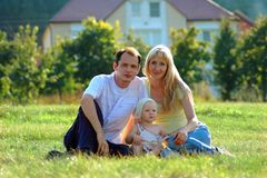 Happy family sits on meadow Stock Photo