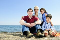 Happy family sitting at beach Stock Photography