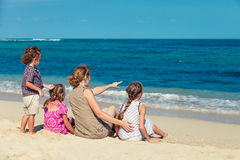 Happy family sitting at the beach Stock Photography