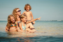 Happy family sitting on the beach Stock Photos