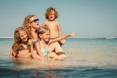 Happy family sitting on the beach Stock Photos
