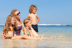 Happy family sitting on the beach Stock Photo