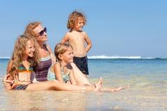 Happy family sitting on the beach Stock Photo