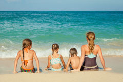 Happy family sitting on the beach Stock Photography