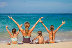Happy family sitting on the beach Royalty Free Stock Image