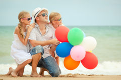 Happy family sitting on the beach at the day time. Royalty Free Stock Photography