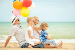 Happy family sitting on the beach at the day time. Stock Images