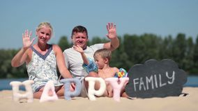 Happy family sitting on the beach and waving hello stock video footage