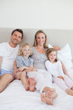 Happy family sitting on the bed Stock Photo