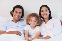 Happy family sitting on the bed together Stock Photos