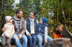Happy family sitting on bench at camp fire Stock Images
