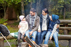 Happy family sitting on bench at camp fire Royalty Free Stock Photography