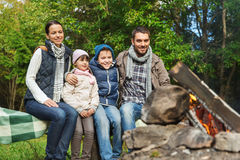Happy family sitting on bench at camp fire Stock Photos
