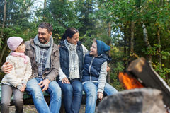 Happy family sitting on bench at camp fire Royalty Free Stock Image