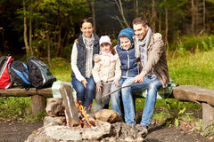Happy family sitting on bench at camp fire Stock Image
