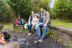 Happy family sitting on bench at camp fire Royalty Free Stock Images
