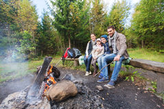 Happy family sitting on bench at camp fire Royalty Free Stock Photos