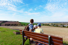 Happy family sitting on bench at meadow at summer day Royalty Free Stock Image