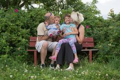 A happy family is sitting on the bench and posing Royalty Free Stock Images