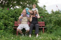 A happy family is sitting on the bench and posing Royalty Free Stock Image