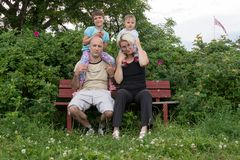 A happy family is sitting on the bench and posing Stock Image