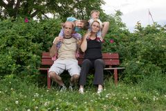 A happy family is sitting on the bench and posing Royalty Free Stock Photo