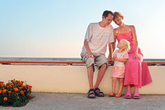 Happy family sitting on bench on resort Royalty Free Stock Photos