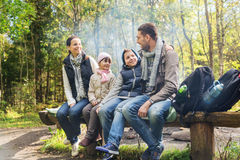 Happy family sitting on bench and talking at camp Stock Photos