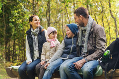 Happy family sitting on bench and talking at camp Stock Photography