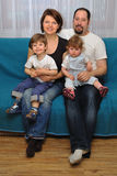 Happy family sitting on blue sofa Stock Photo