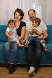Happy family sitting on blue sofa Stock Photos