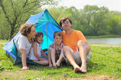 Happy family sitting in blue tent Stock Photo