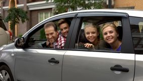 Happy family sitting in car and smiling into camera, automobile buying service royalty free stock photography
