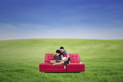 Happy family sitting on a couch on a green meadow Stock Images