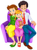 A happy family sitting on a couch Stock Image