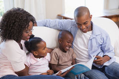 Happy family sitting on couch together reading book Royalty Free Stock Images