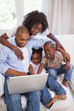 Happy family sitting on couch together using laptop Stock Image