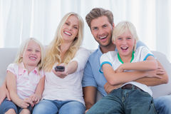 Happy family sitting on couch Royalty Free Stock Images