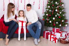 Happy family sitting in decorated living room with Christmas tre Royalty Free Stock Photography