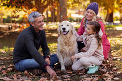 Happy family sitting with dog at park Stock Photos