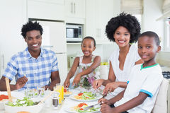 Happy family sitting down to dinner together Royalty Free Stock Photography