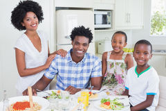 Happy family sitting down to dinner together Royalty Free Stock Photos