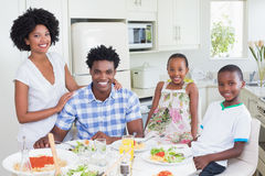 Happy family sitting down to dinner together Royalty Free Stock Images