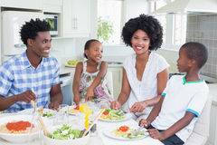 Happy family sitting down to dinner together Stock Photo